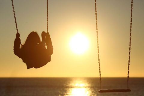 back view of woman on a swing at sunset